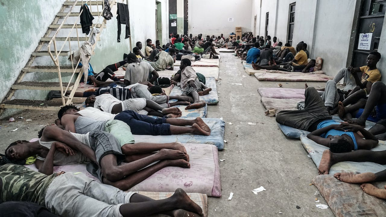 Illegal immigrants are seen at a detention centre in Zawiyah, 45 kilometres west of the Libyan capital Tripoli. (Photo by Taha JAWASHI / AFP)