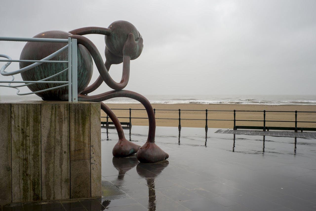 Het bronzen beeld 'Huilende reus' van de Amerikaanse beeldhouwer Tom Otterness, van museum Beelden aan Zee in Scheveningen op de boulevard.