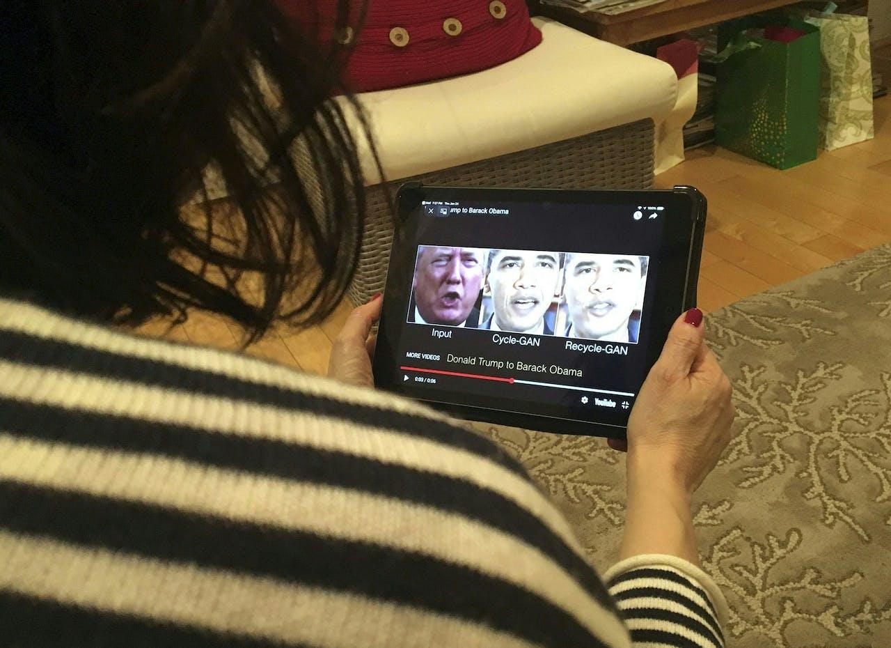 Een vrouw bekijkt deepfakes op een tablet.
