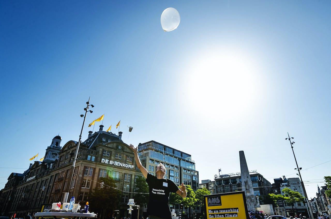 Onderzoekers van Wageningen Universiteit en AMS Institute laten een weerballon op vanaf de Dam.
