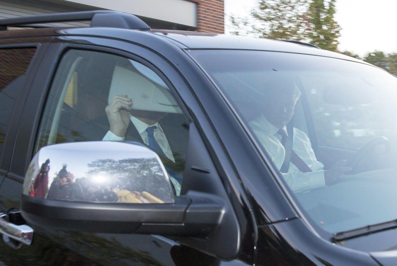 Paul Manafort bedekt zijn gezicht bij het verlaten van zijn huis