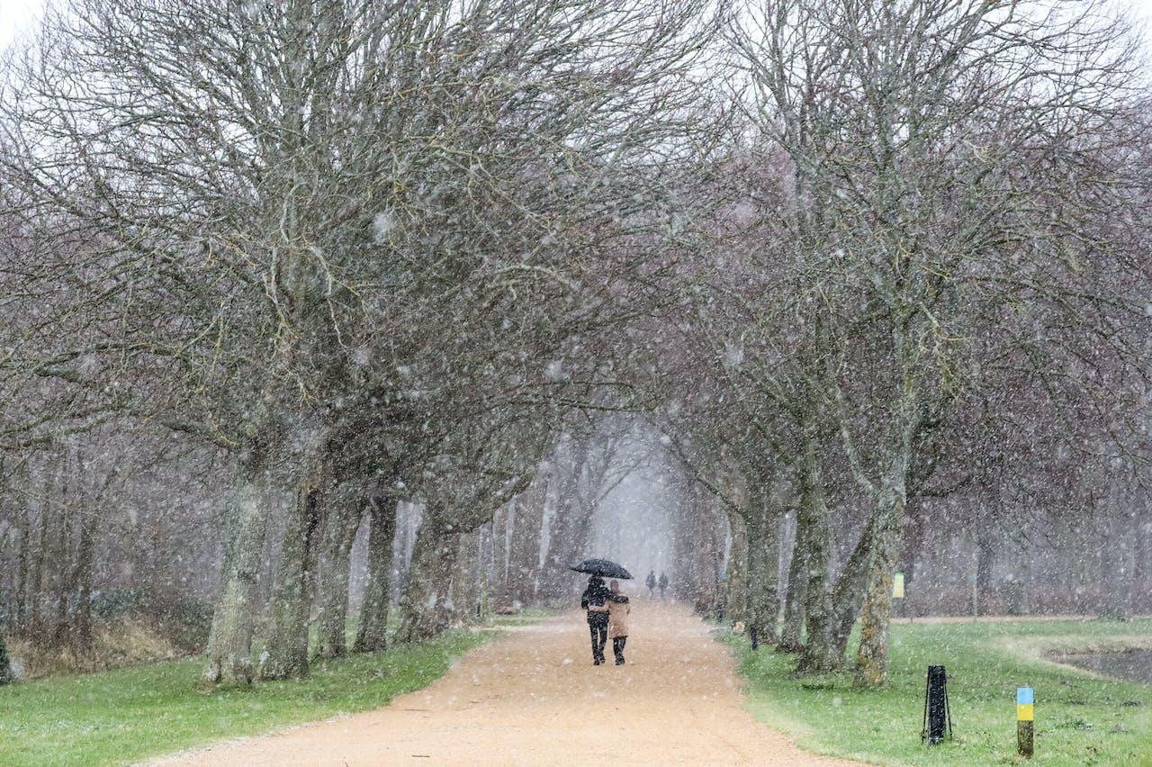 Wandelaars lopen in de sneeuw in Vlissingen.