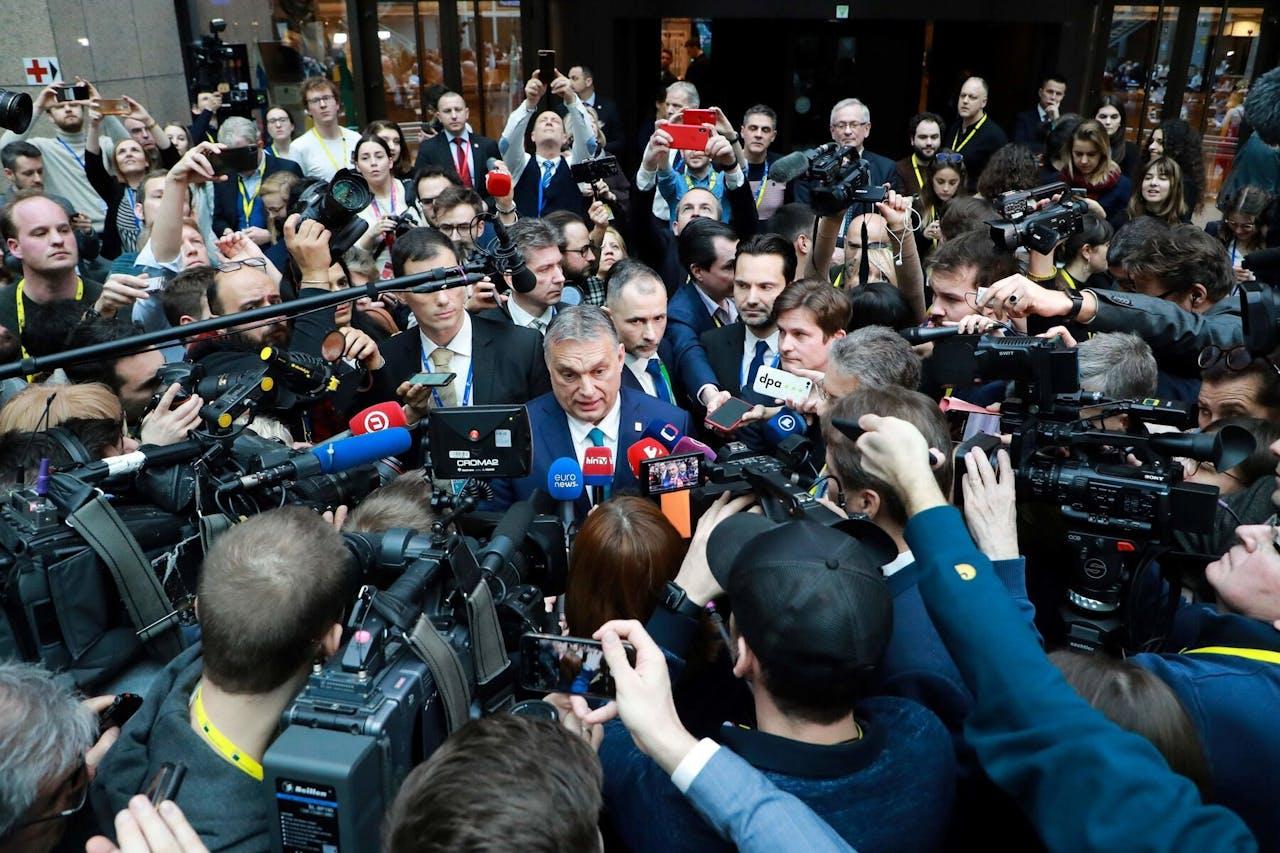 Hongaarse premier Viktor Orbán laat zich zien in de perszaal tijdens een pre-corona EU-top. Eén van de makers van Europamania is in de linkerbovenhoek te vinden (met geel bandje om zijn nek).