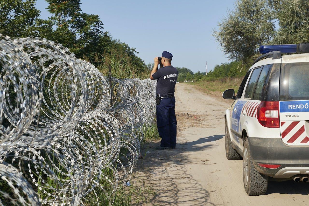 ROSZKE - Hongaarse agenten bewaken de grens met Serbie. ANP Pierre Crom
