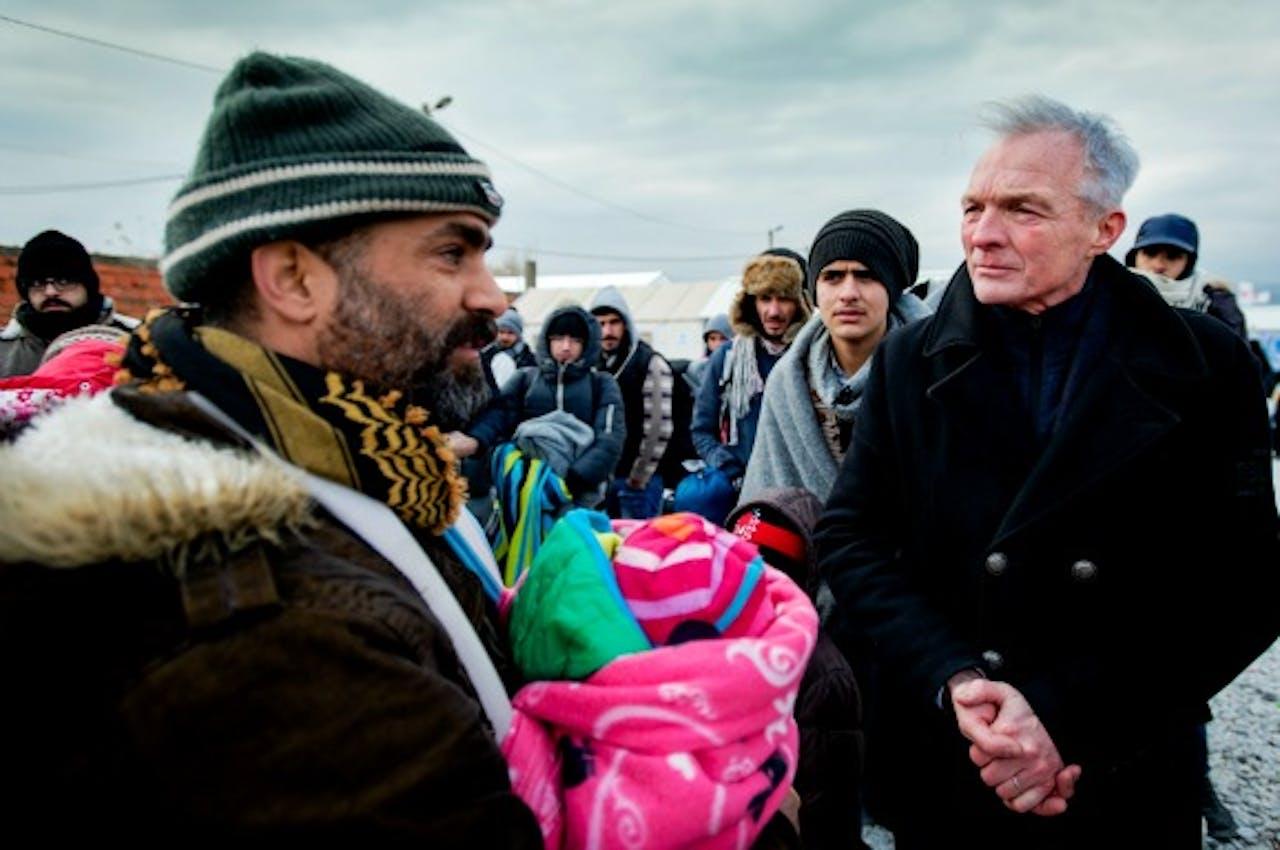 Kinderombudsman Marc Dullaert praat met vluchtelingen met kinderen tijdens een bezoek aan het vluchtelingenkamp Vinojug. Foto: ANP
