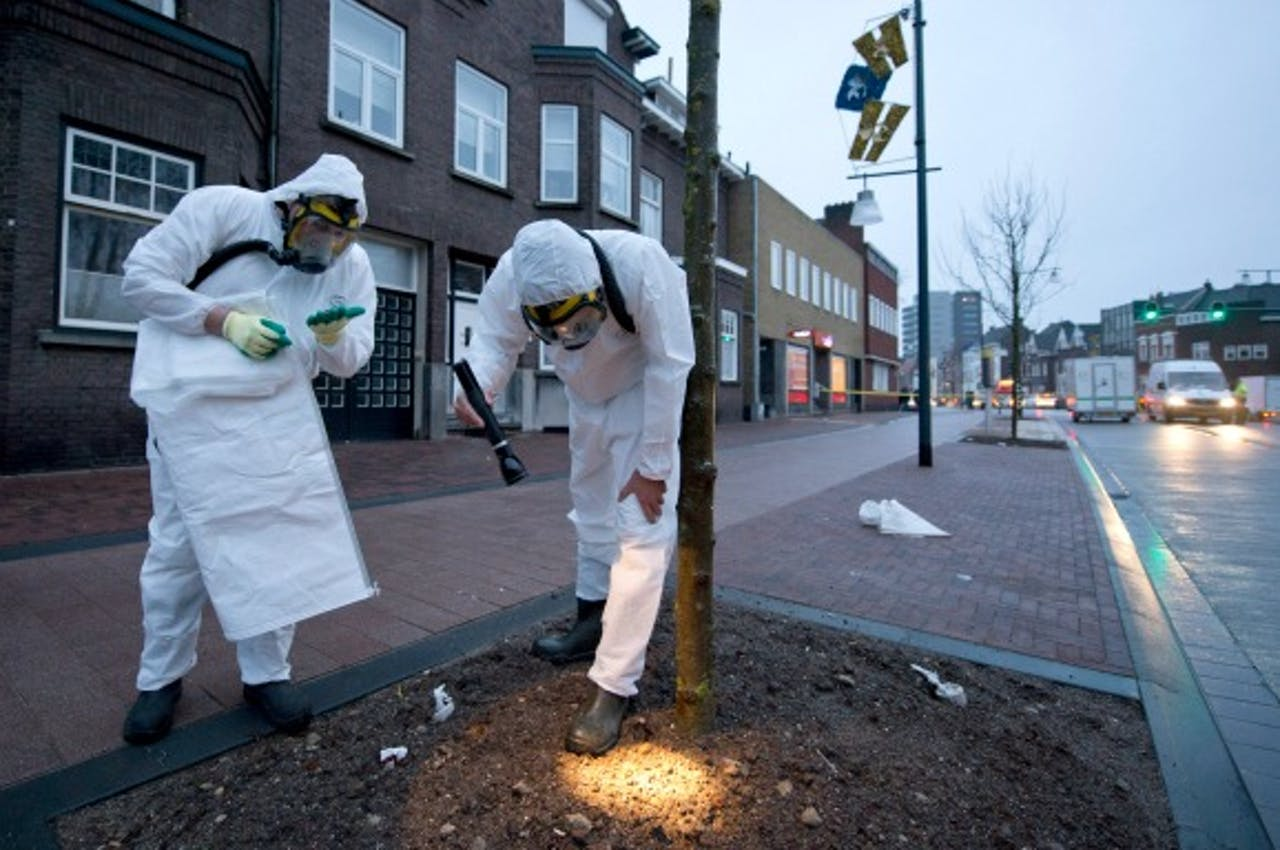 Twee mannen ruimen asbest op in Roermond nadat dit vrijkwam bij een grote brand in een loods in 2014. Foto: ANP
