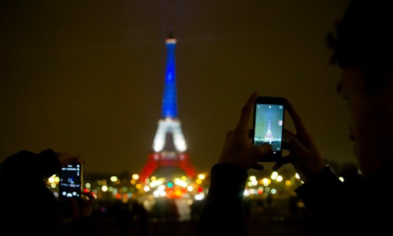 De Eiffeltoren in de Franse nationale kleuren, ter nagedachtenis aan de slachtoffers van de aanslagen van 13 november in Parijs. (Foto: ANP)