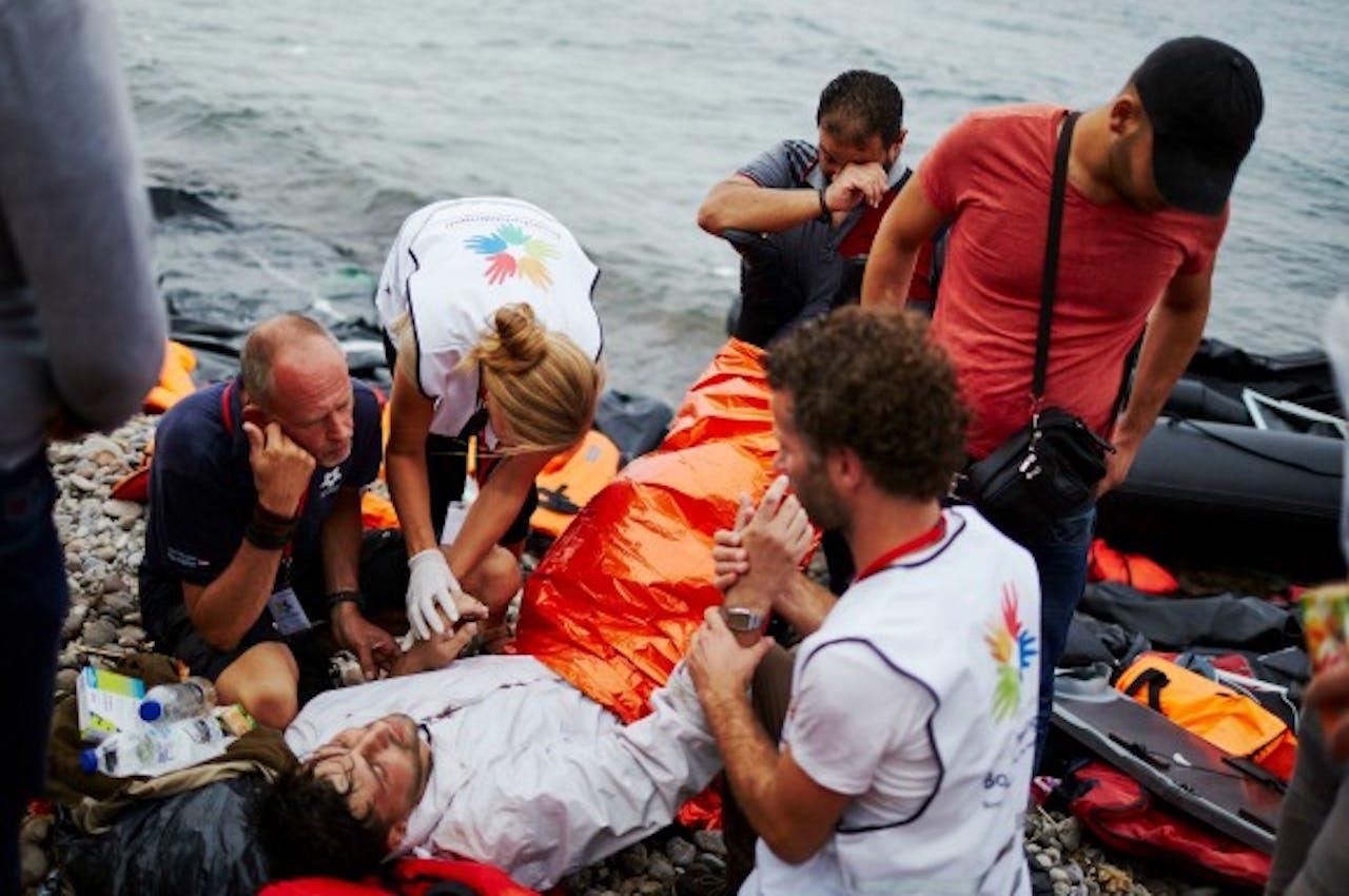 Vrijwilligers van de Nederlandse Stichting Hulpactie Bootvluchtelingen helpen vluchtelingen bij aankomst op Lesbos. Foto: ANP