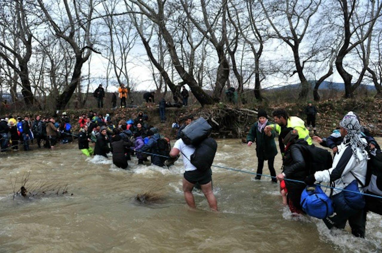Vluchtelingen steken de rivier bij de Grieks-Macedonische grens over. Foto ANP