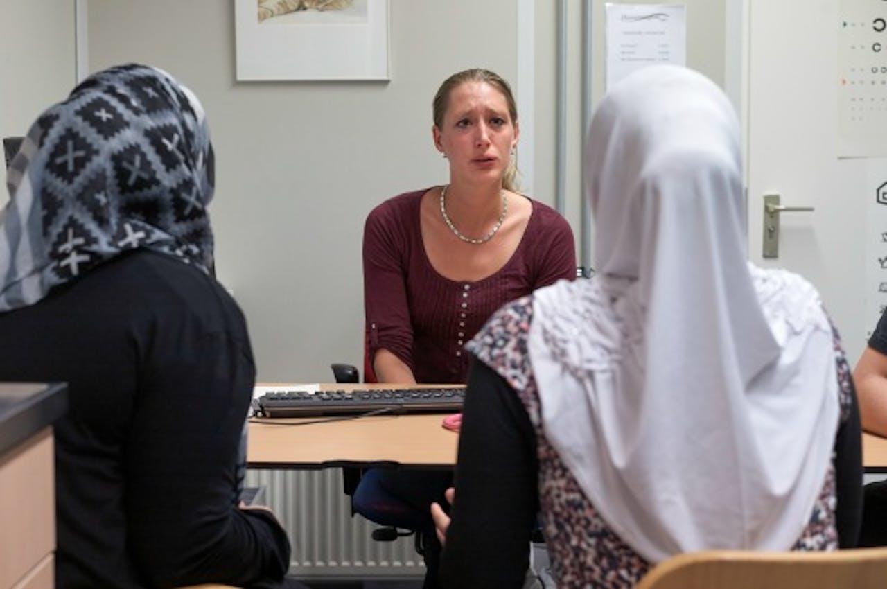 Een huisarts in gesprek met patiënten. (Foto: ANP)