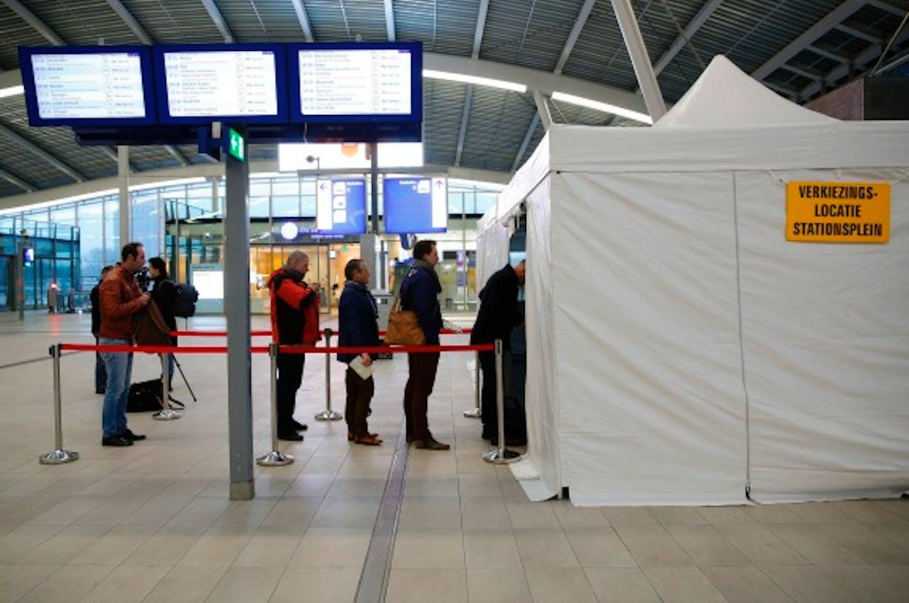 Eerste stemmers staan in alle vroegte in de rij voor de stemtent op het station. Foto: ANP