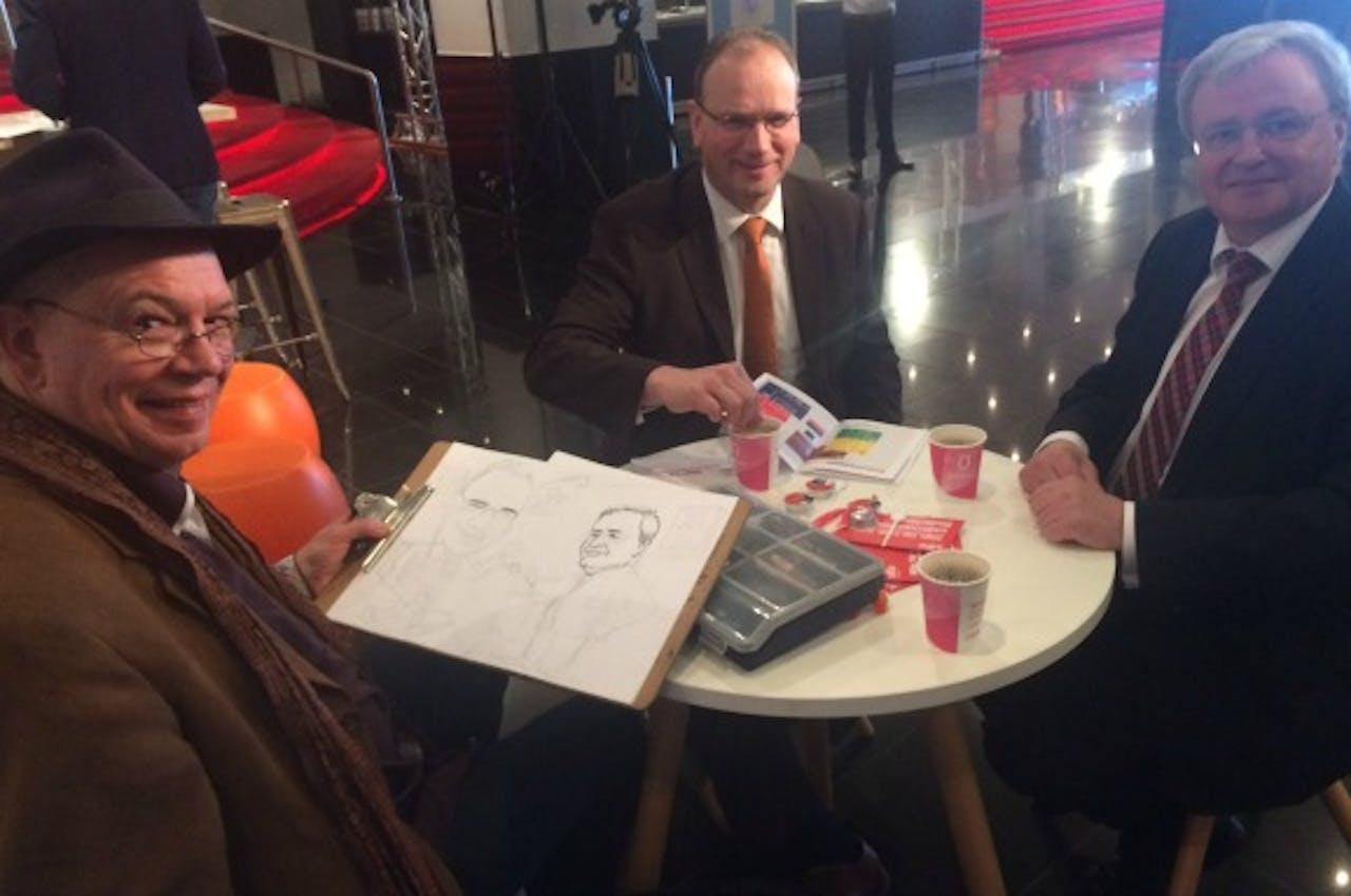 Cartoonist tekent snel FNV-leider Heerts (midden) en MKBNL-voorman Van Straalen. Foto BNR / Elfanie toe Laer