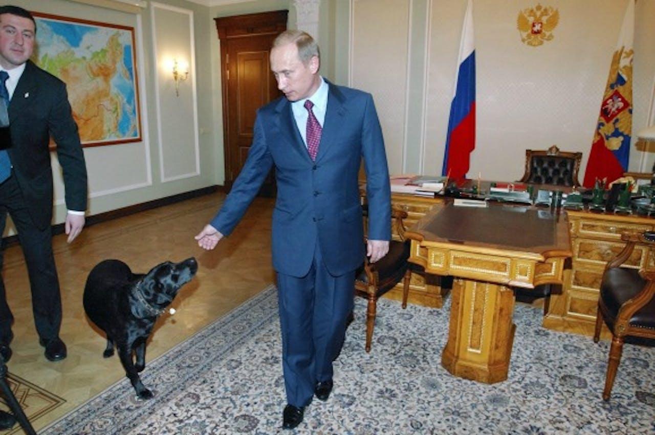 Poetin aait zijn hond Conny. Foto ANP