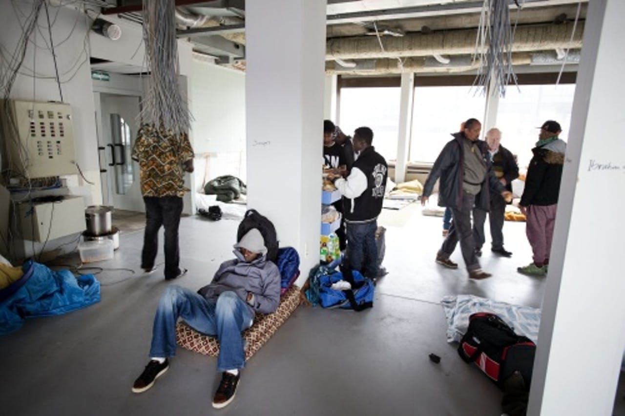 ANP Uitgeprocedeerde asielzoekers in een gekraakt kantoorpand in Amsterdam-West.