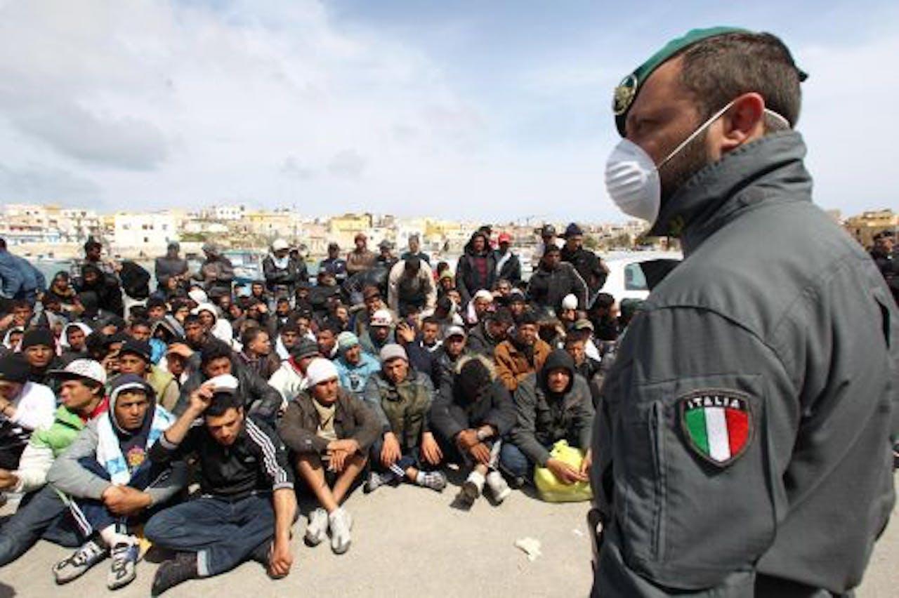 Een Italiaanse politieagent houdt bootvluchtelingen in de gaten. EPA