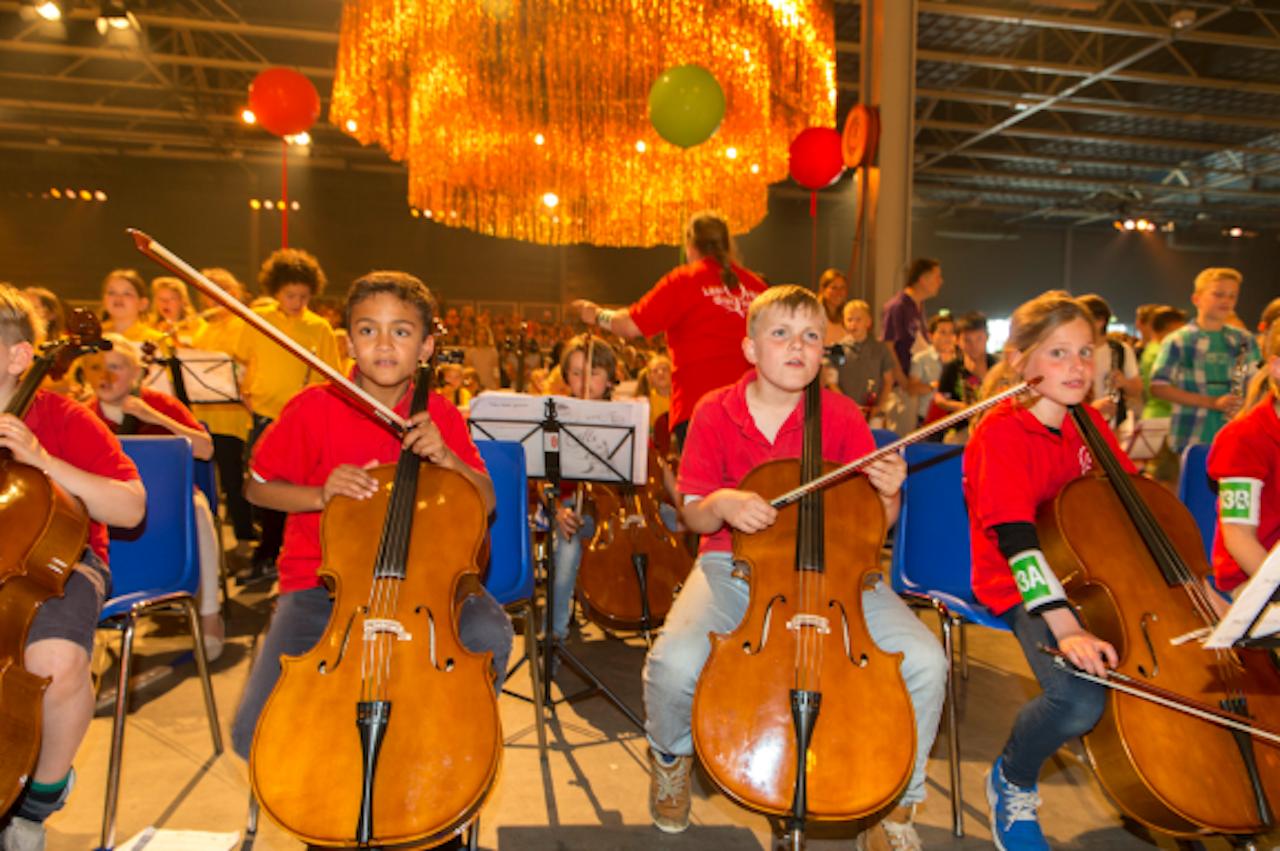 Kinderen musiceren tijdens de tweede editie van het eindconcert van Kinderen Maken Muziek, juni dit jaar. Dit initiatief biedt zoveel mogelijk kinderen de mogelijkheid in aanraking te komen met een muziekinstrument en samen muziek te maken. Bij dit concert was ook koningin Máxima aanwezig.