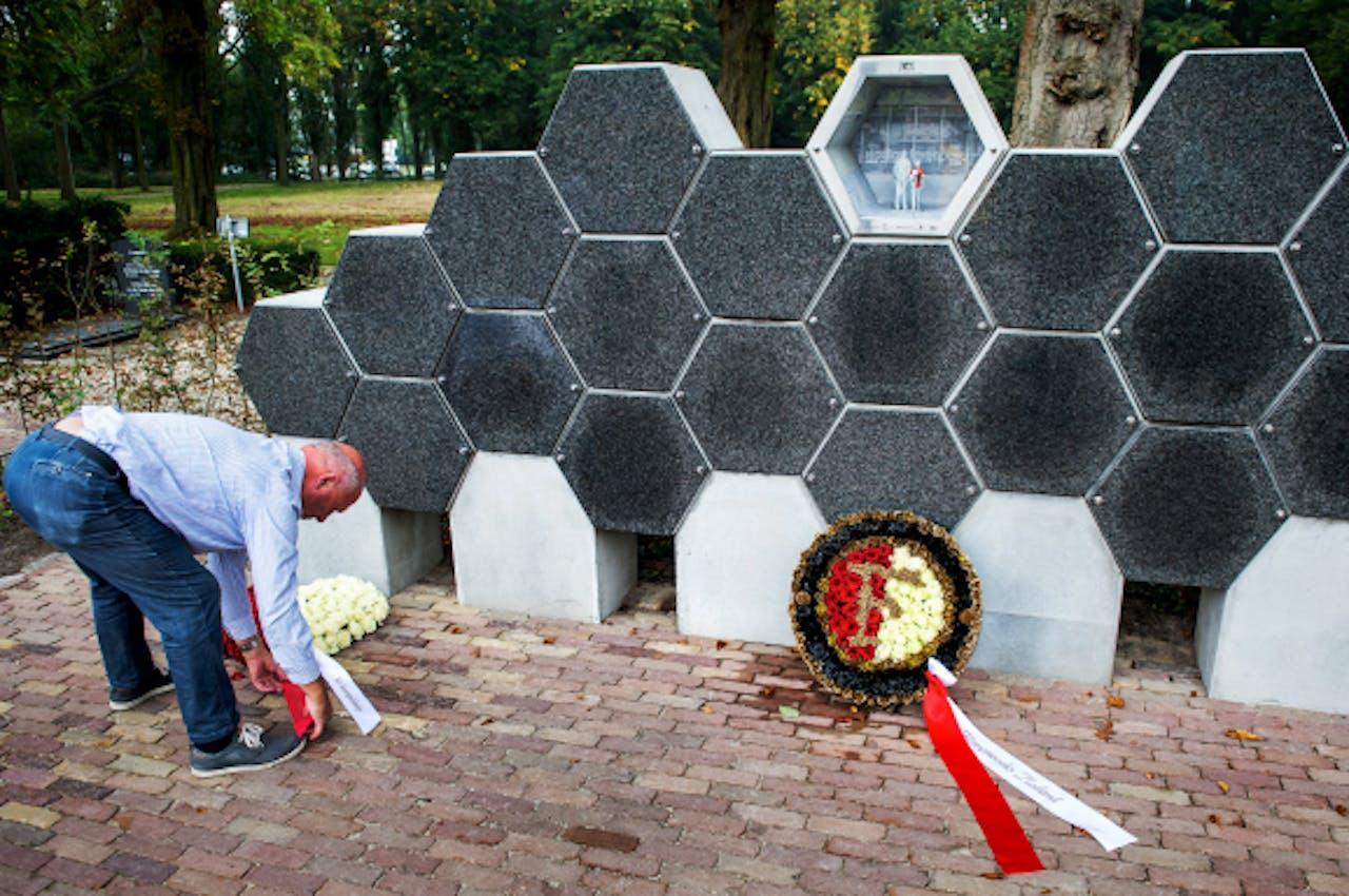 Foto: ANP - Een man legt bloemen bij de urnenmuur in het Feyenoordvak op de Zuiderbegraafplaats in Rotterdam.