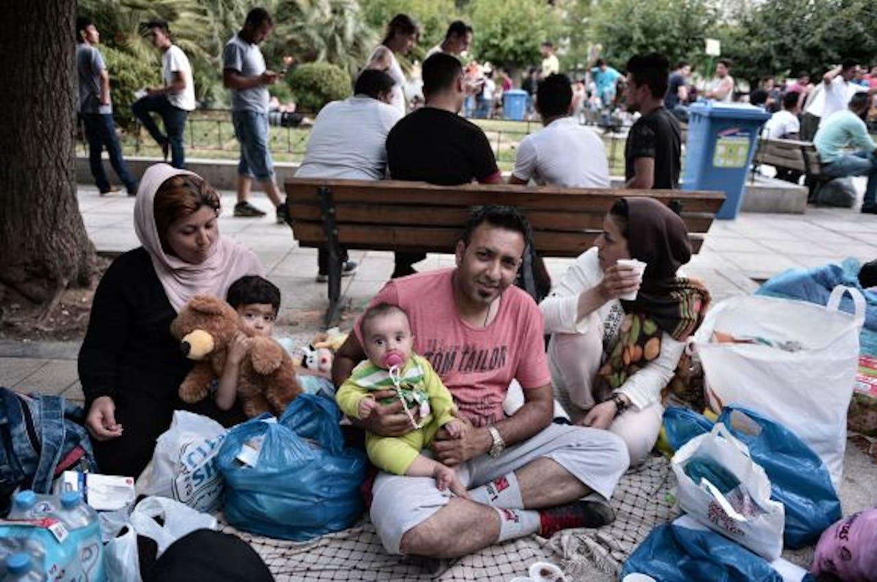 Een Afghaans gezin op een plein in Athene. Foto: ANP/AFP