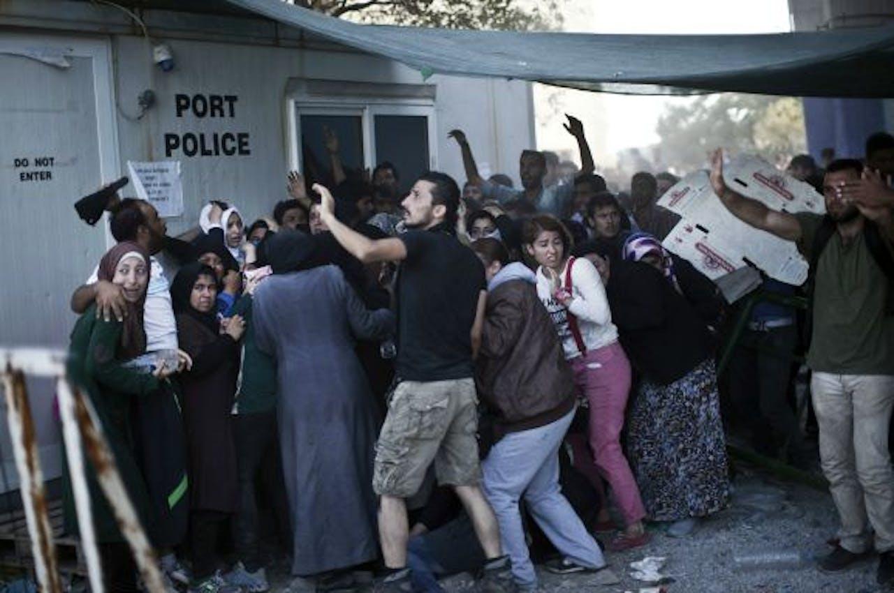 Afghaanse en Syrische vluchtelingen proberen zich te beschermen tegen rondvliegende stenen in de haven van Lesbos. Foto AFP