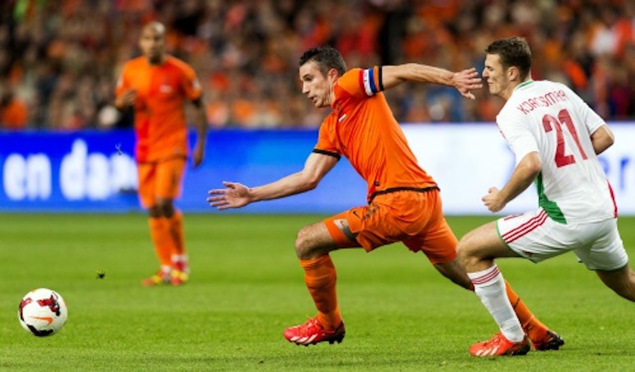 Robin van Persie (L) in duel met Zsolt Korcsmar (R) tijdens de WK-kwalificatiewedstrijd tegen Hongarije. ANP