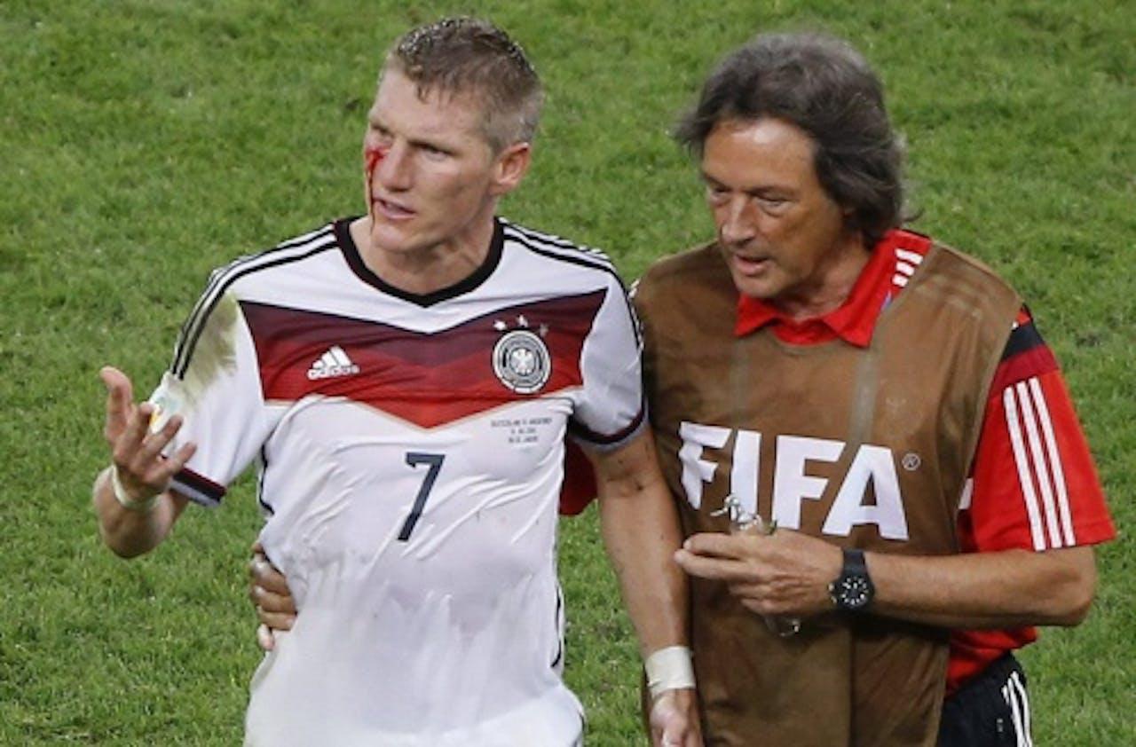 EPA Clubarts Hans-Wilhelm Müller-Wohlfahrt (R) helpt Bastian Schweinsteiger (L) van het veld.