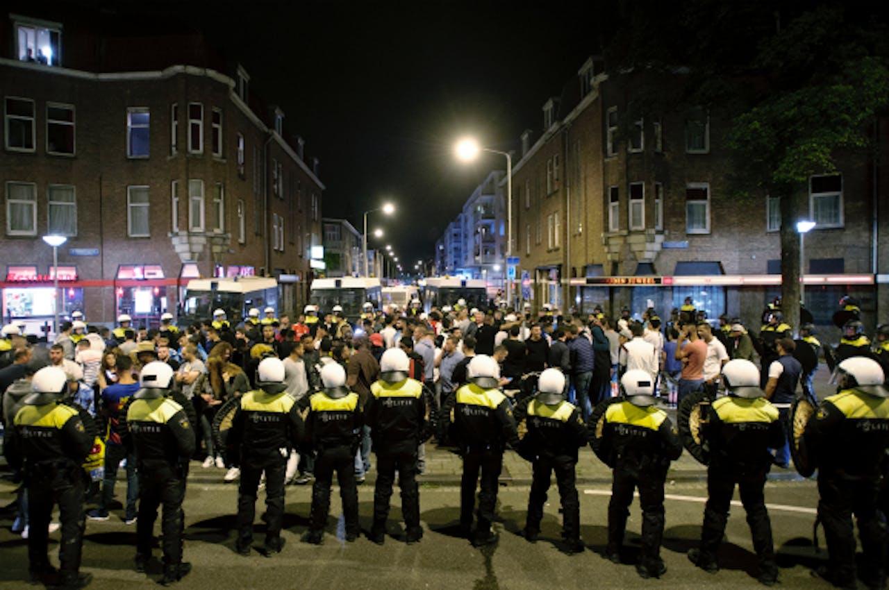 Foto: ANP - ME'ers vormen een linie om mensen in te sluiten in de Haagse Schilderswijk