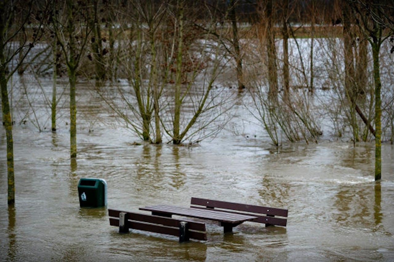 Archieffoto 2011: Een bankje staat onder water in het Limburgse Vlodrop