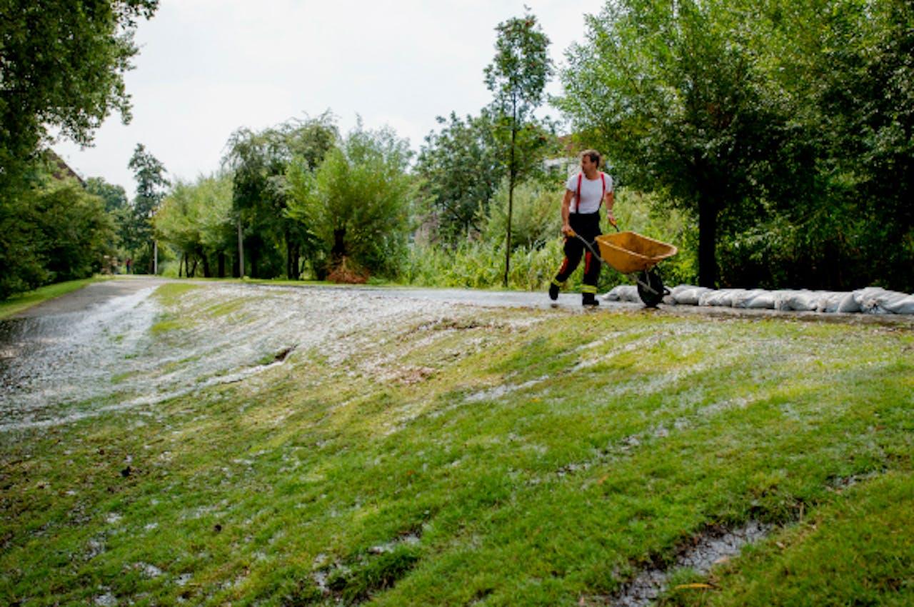 Burgers helpen de brandweer met het plaatsen van zandzakken bij het dijkje in Assumburg dat overstroomt