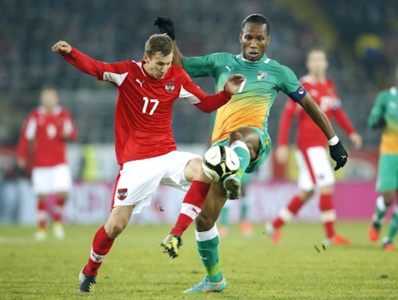 Florian Klein (L) van Oostenrijk in duel met Didier Drogba (R) van Ivoorkust. EPA