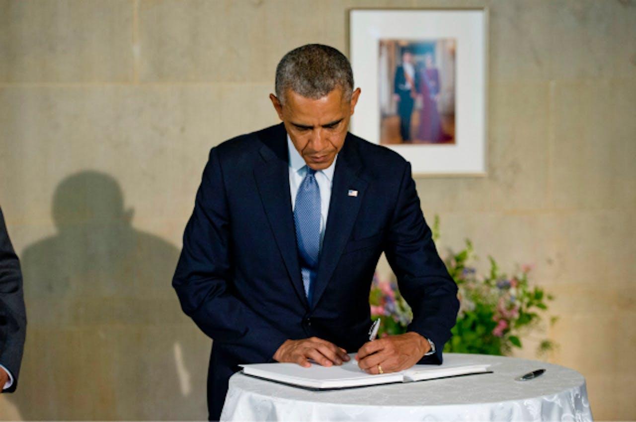 Obama tekent het condoleanceregister voor de slachtoffers