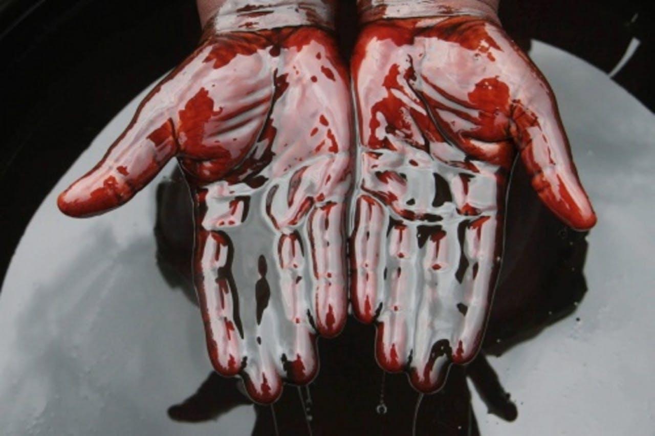 Een man bedekt zijn handen in ruwe olie. EPA