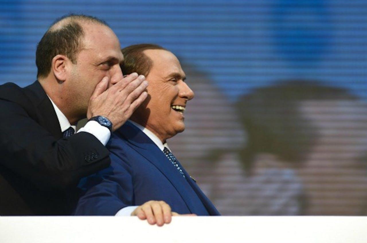 Berlusconi krijgt iets in zijn oor gefluisterd van partijleider Angelino Alfano.