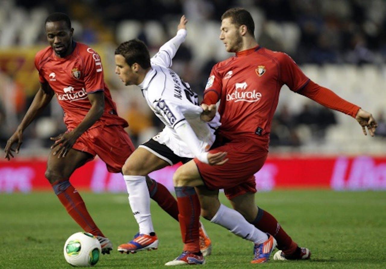 Juan Bernat (M) van Valencia in duel met David Timor (R) en Roland Lamah (L) van Osasuna. EPA