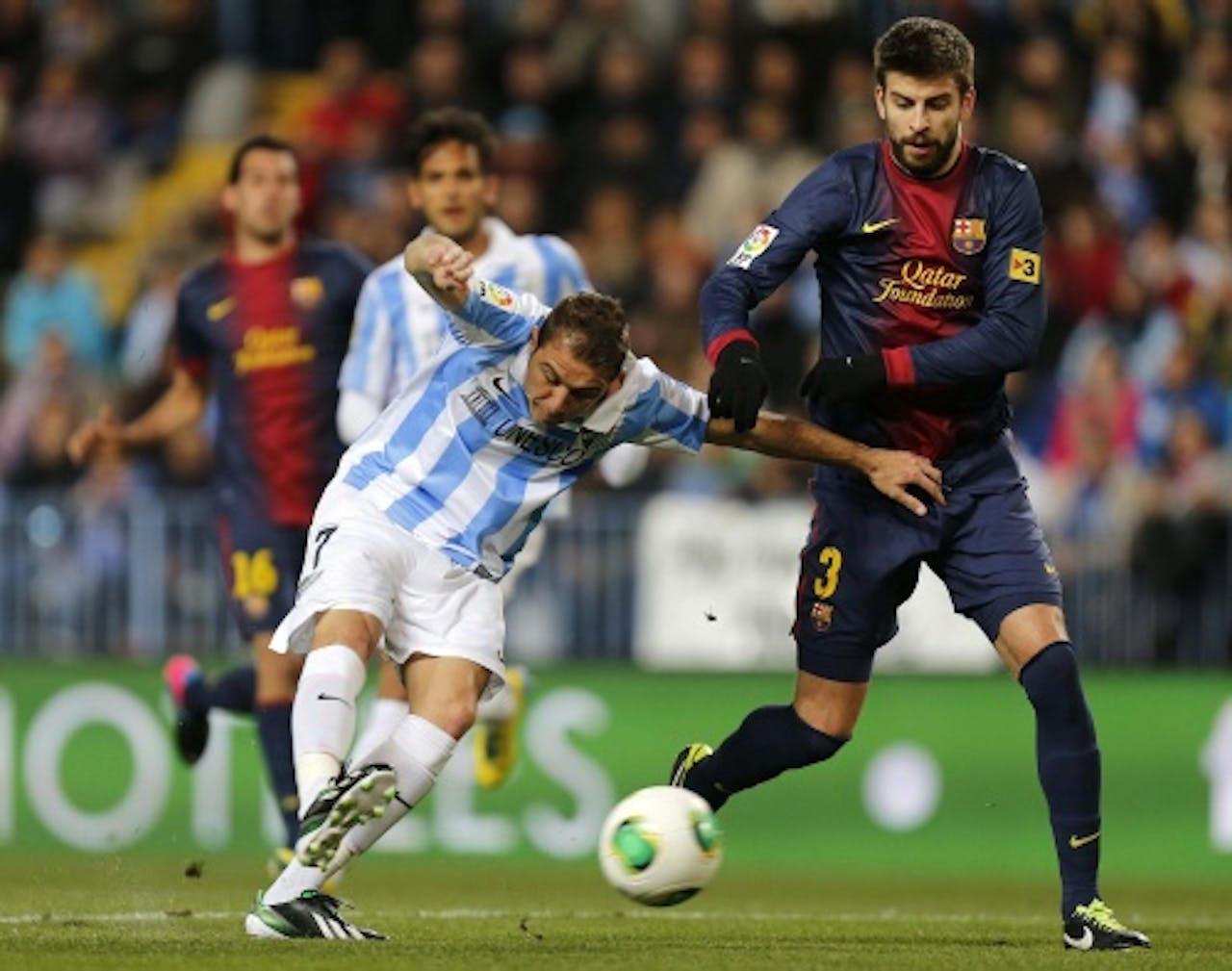 Gerard Pique (R) van Barcelona in duel met Joaquin Sanchez (L) van Malaga. EPA