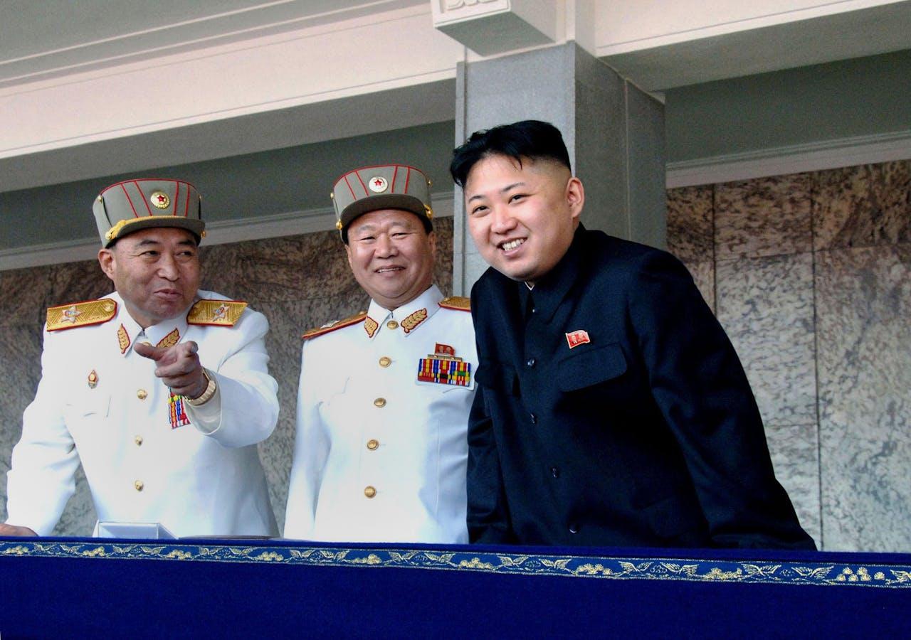 De Noord-Koreaanse leider Kim Jong-Un (R) lacht samen met legerleider Ri Yong-Ho (L) en een andere militaire officier tijdens een militaire parade voor de 100e verjaardag van de voormalig Noord-Koreaanse leider Kim Il Sung op het Kim Il Sung plein in Pyongyang.