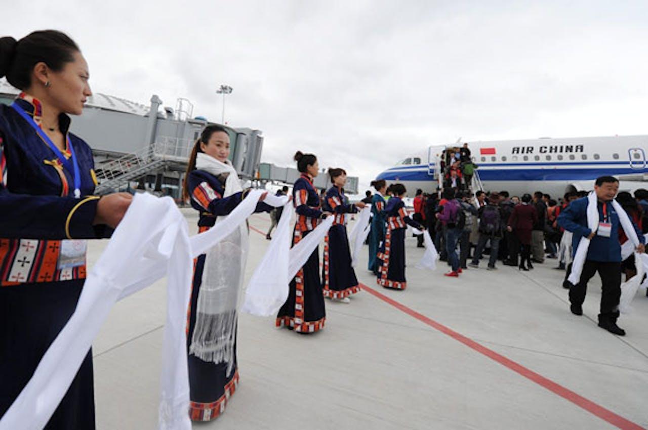 Tibetaanse vrouwen verwelkomen de eerste passagiers op luchthaven Daocheng Yading.