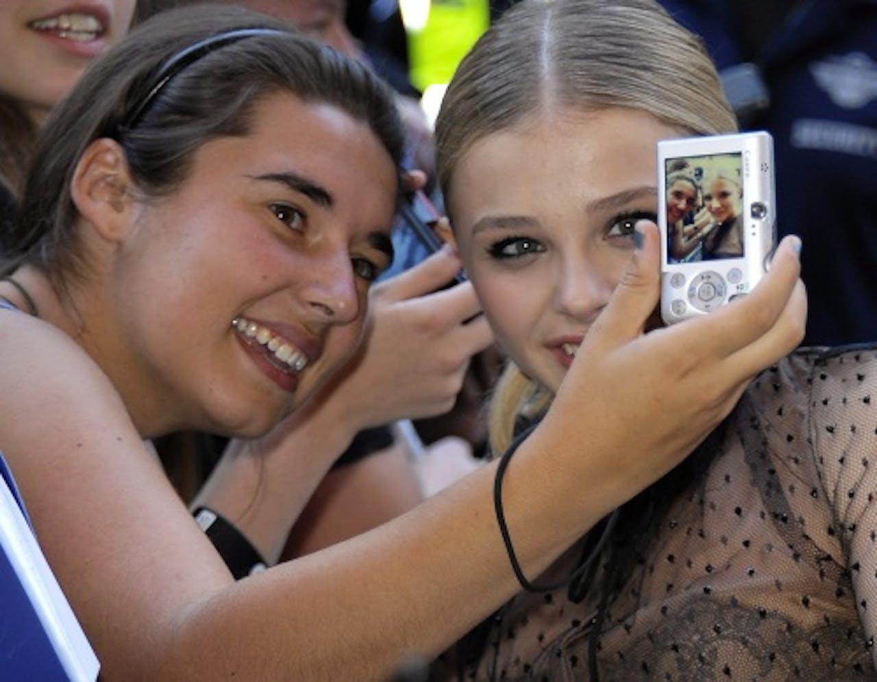 Chloë Grace Moretz (R) met een fan. EPA