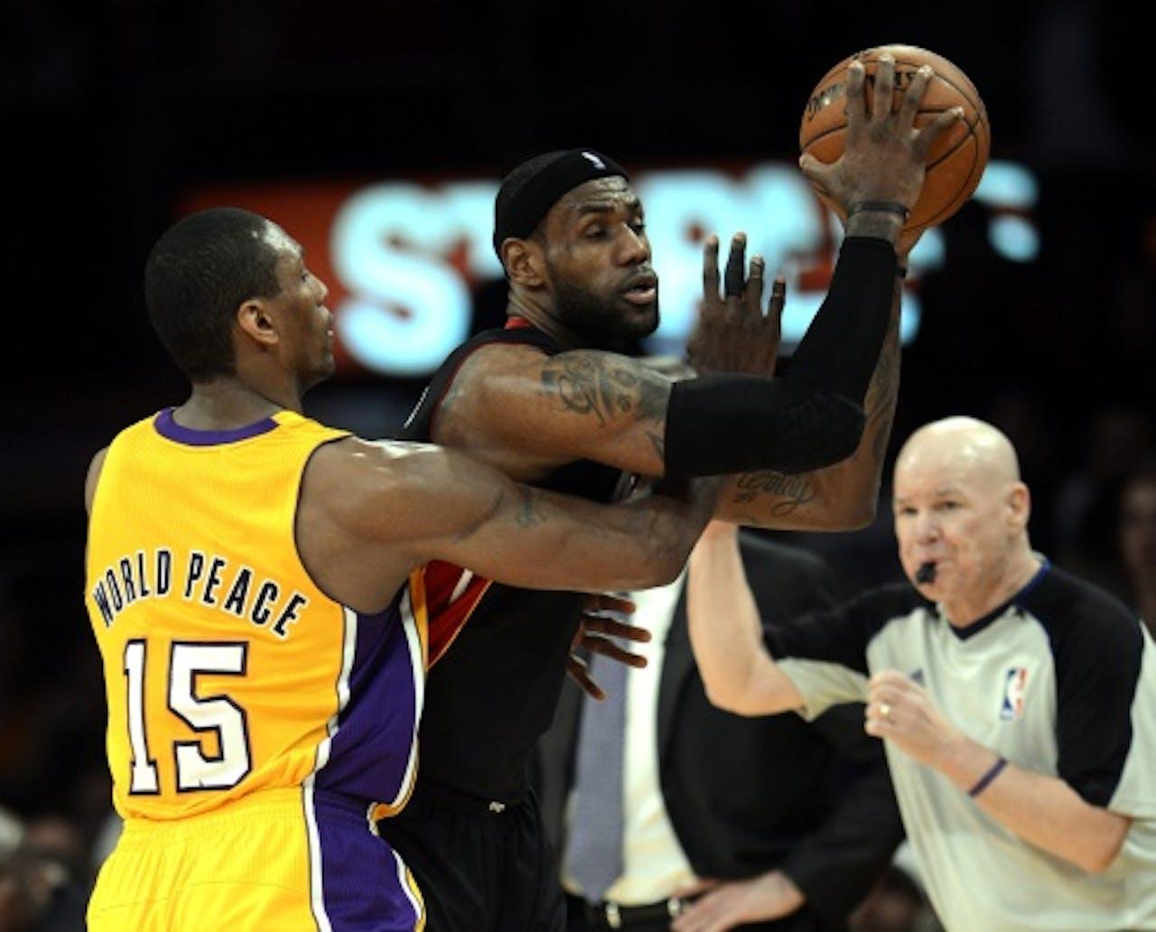 LeBron James (M) van Miami Heat in duel met Metta World Peace (L) van Los Angeles Lakers. EPA