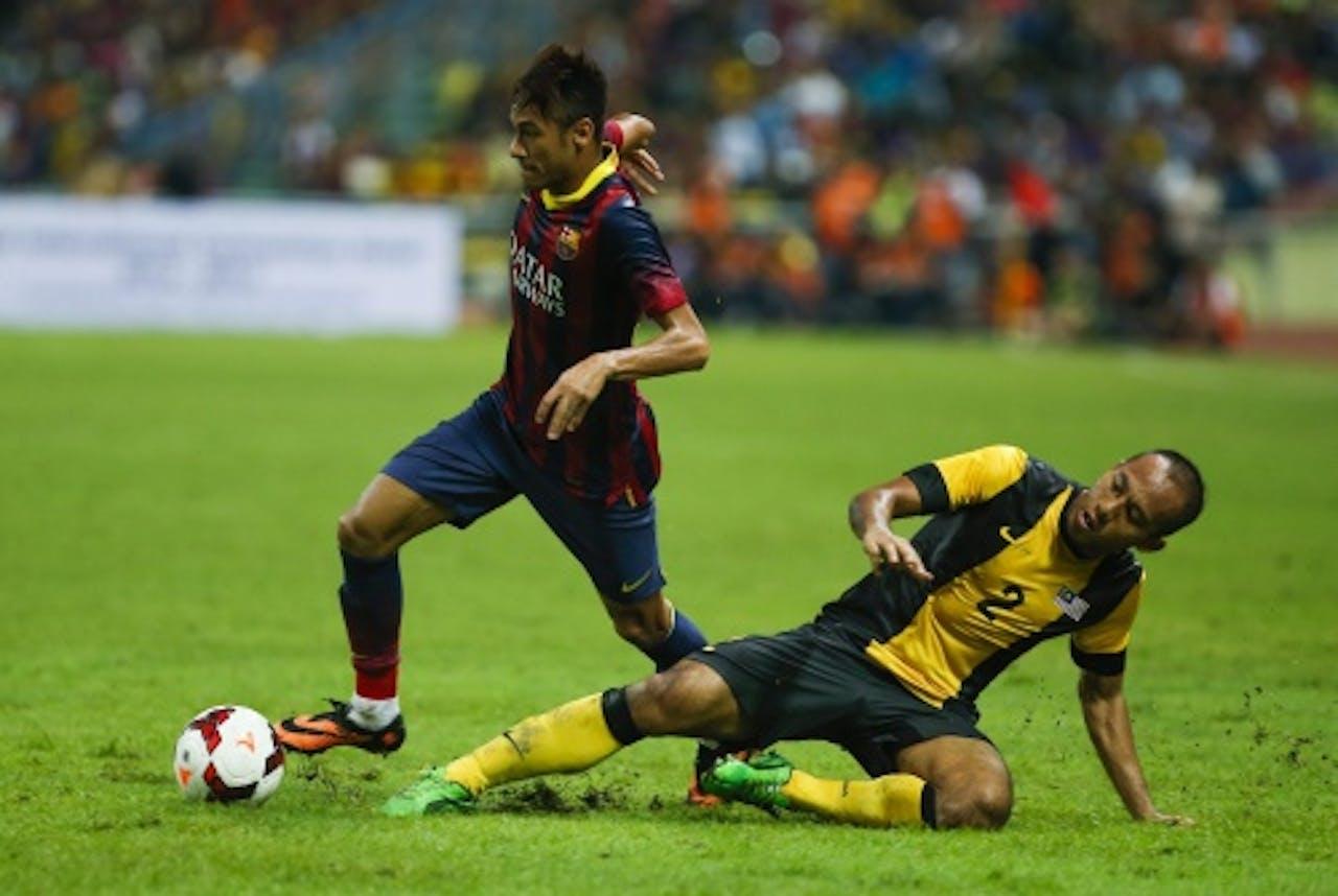 Neymar (L) van FC Barcelona in duel met Mahalli Jasuli van het Maleisische elftal. EPA