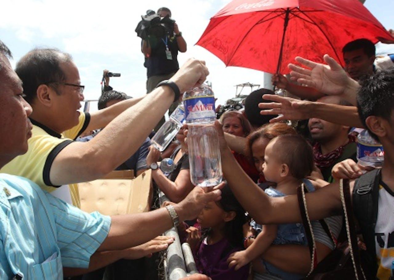 Benigno Aquino deelt water uit aan slachtoffers. EPA