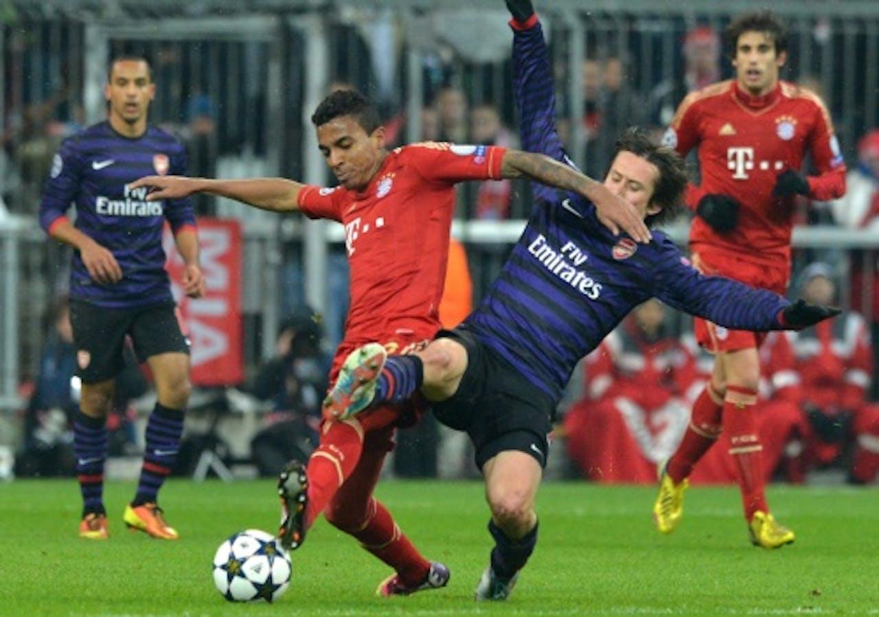 Luiz Gustavo (L) van Bayern München in duel met Tomas Rosicky (R) van Arsenal. EPA