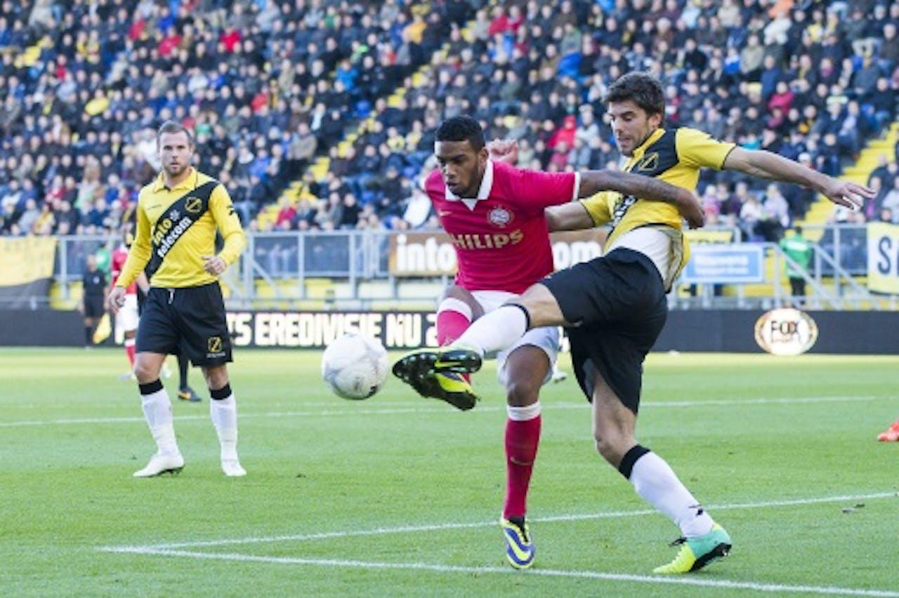 Jürgen Locadia (M) van PSV in duel met Kees Kwakman (R) van NAC. ANP PRO SHOTS