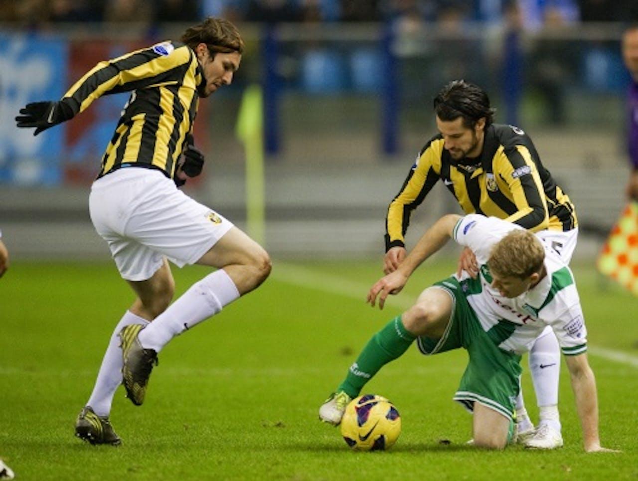 Mike Havenaar (L) en Simon Cziommer (R) van Vitesse in duel met Michael de Leeuw van FC Groningen, ANP