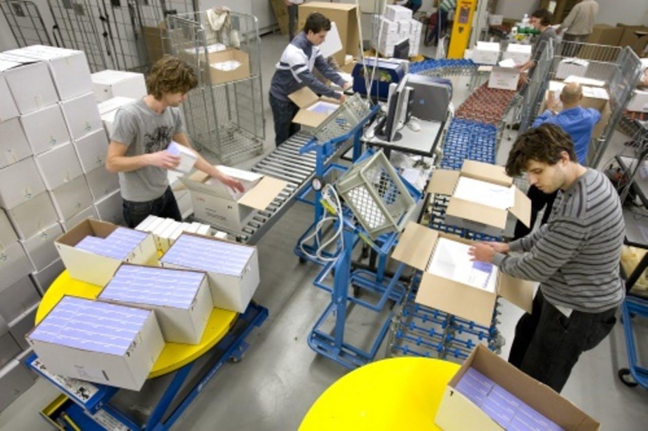 Medewerkers van het Nederlands Vaccin Instituut (NVI) pakken vaccins tegen de Mexicaanse griep in. ANP