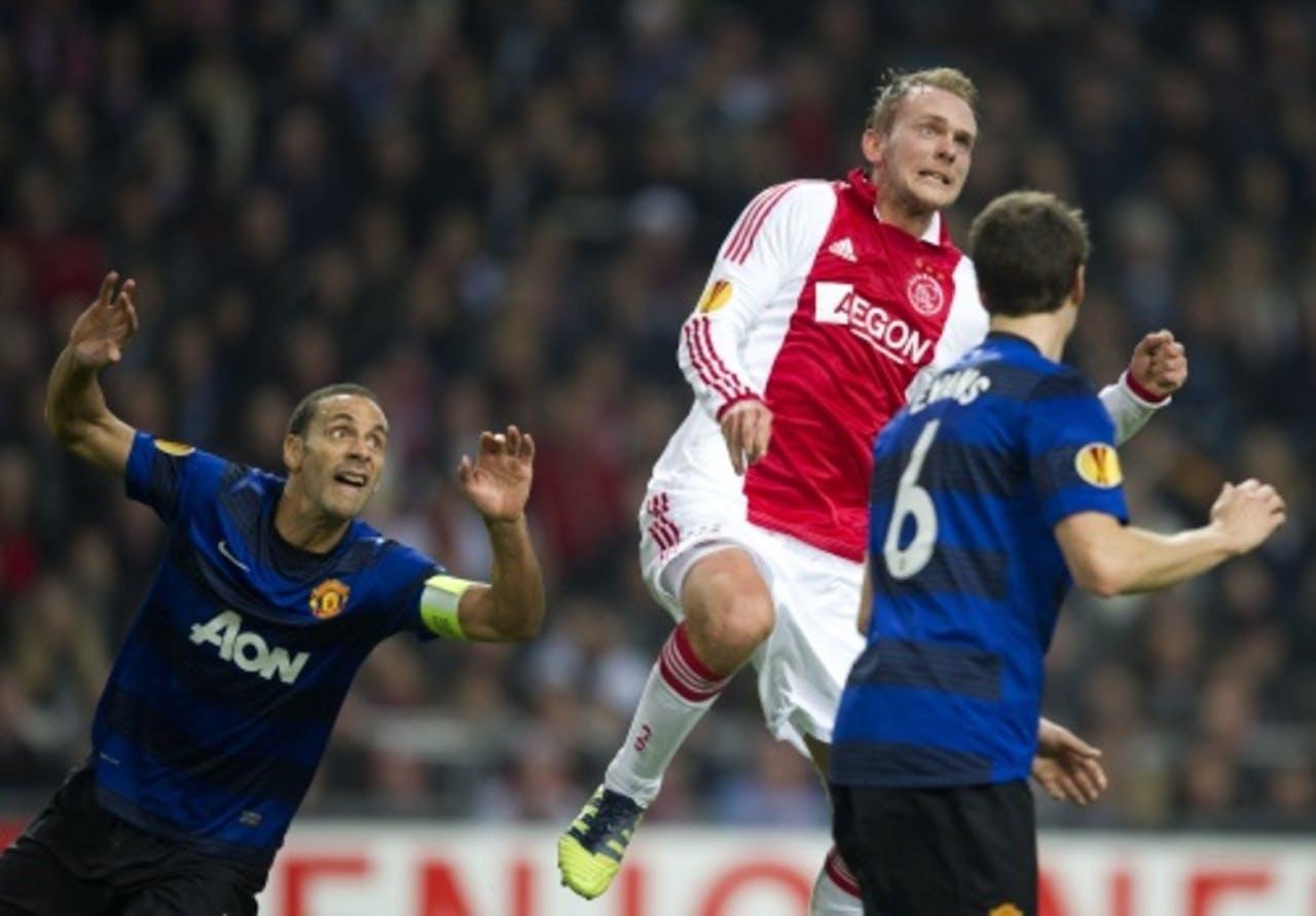 Siem de Jong van Ajax wacht met Rio Ferdinand van Manchester United op de bal. ANP