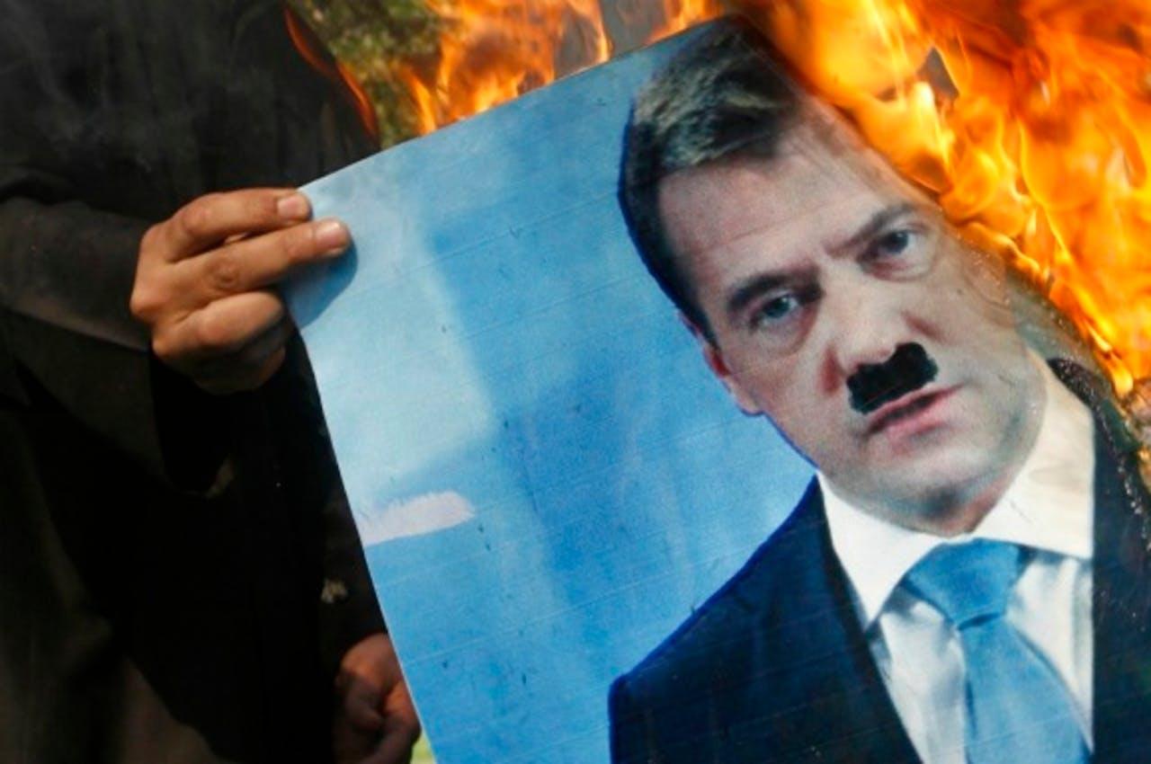 Demonstrant in Syrie steekt een foto Medvedev in brand