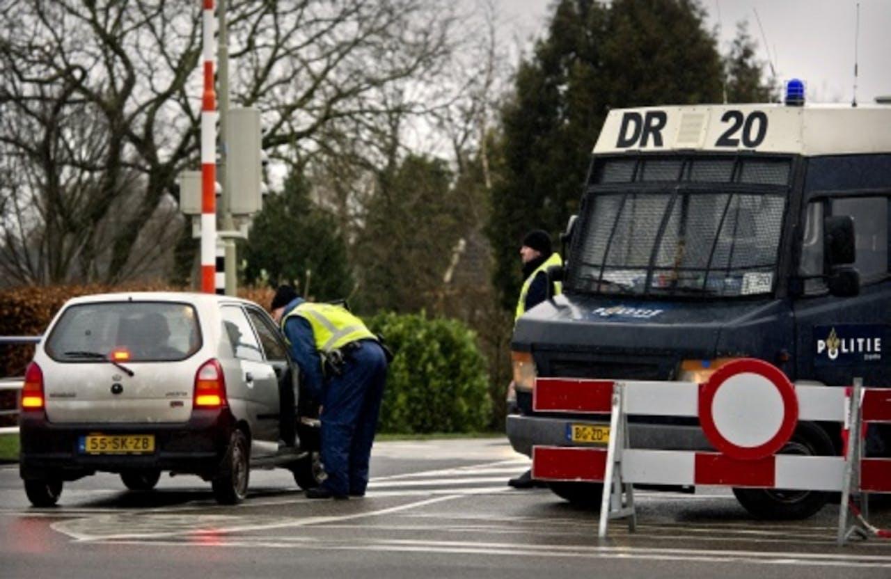 Een agent staat een automobilist te woord in Ten Boer. ANP