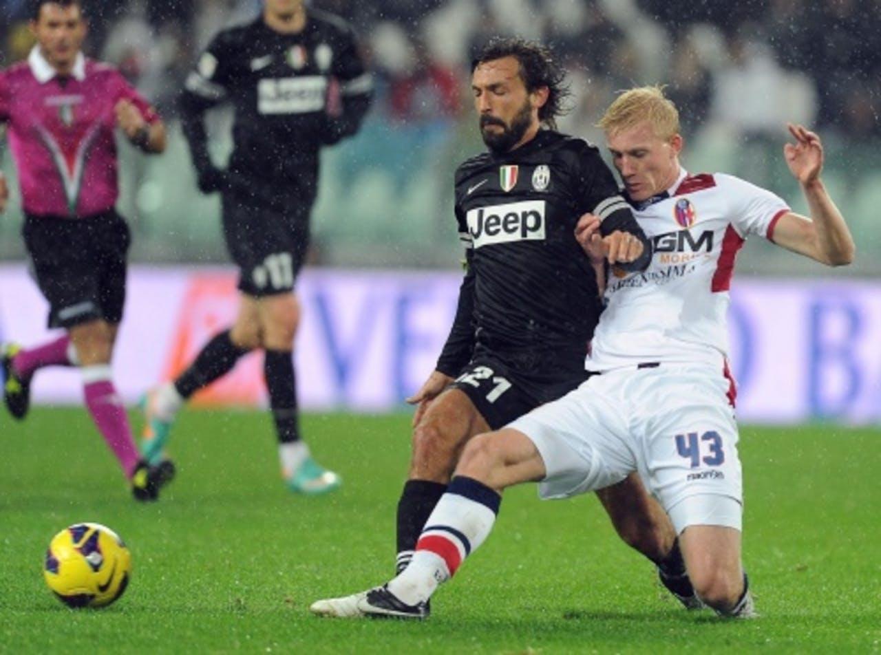 Andrea Pirlo van Juventus in duel met Bologna-speler Frederik Sorensen. EPA
