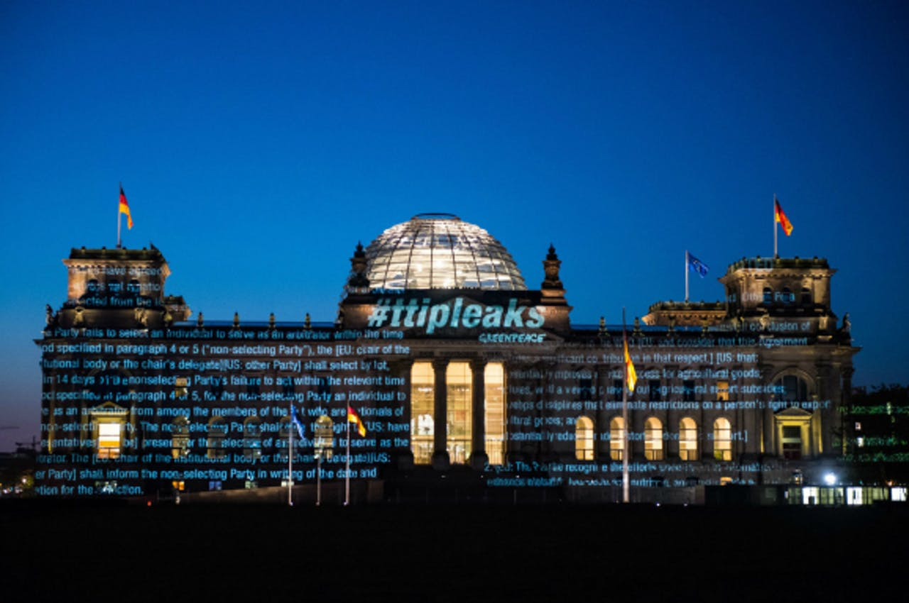 Vanochtend vroeg in Berlijn: Greenpeace projecteert een deel van de tekst uit het TTIP-verdrag op het gebouw van de Rijksdag. ANP/EPA