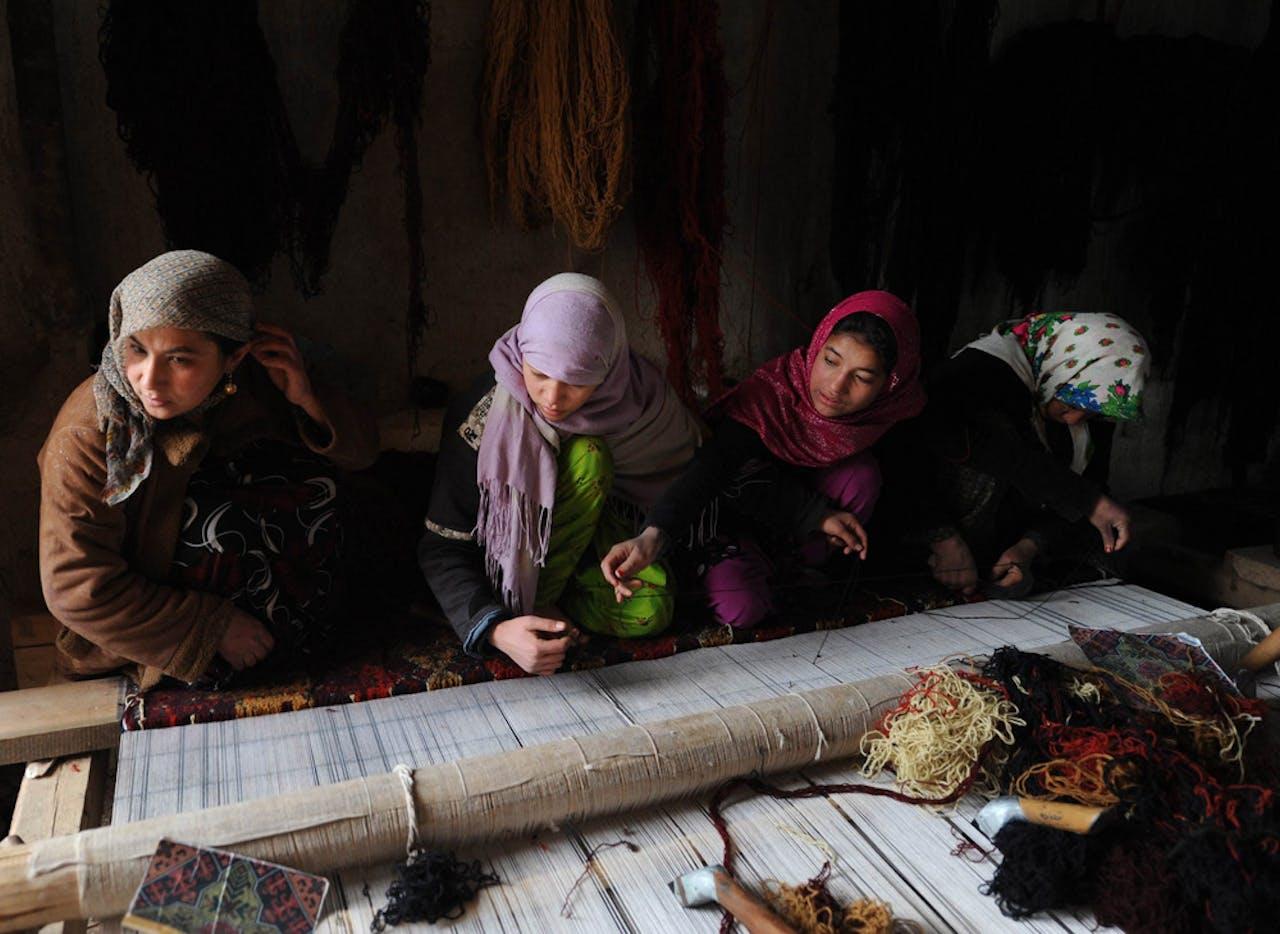 Een Afghaanse vrouwen weven een kleed